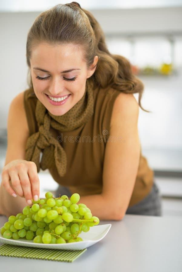 Gelukkige jonge huisvrouw die druif eten royalty-vrije stock fotografie