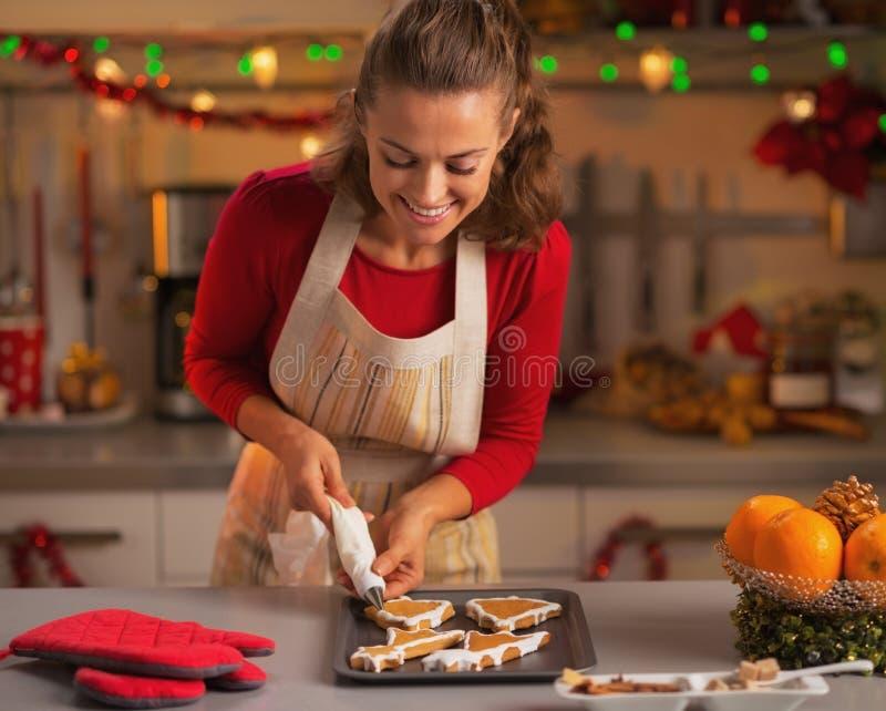 Gelukkige jonge huisvrouw die Kerstmiskoekjes in keuken verfraait royalty-vrije stock foto's