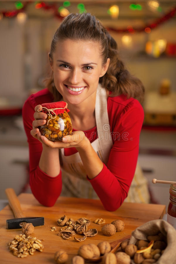 Gelukkige jonge huisvrouw die kruik met honingsnoten tonen royalty-vrije stock fotografie