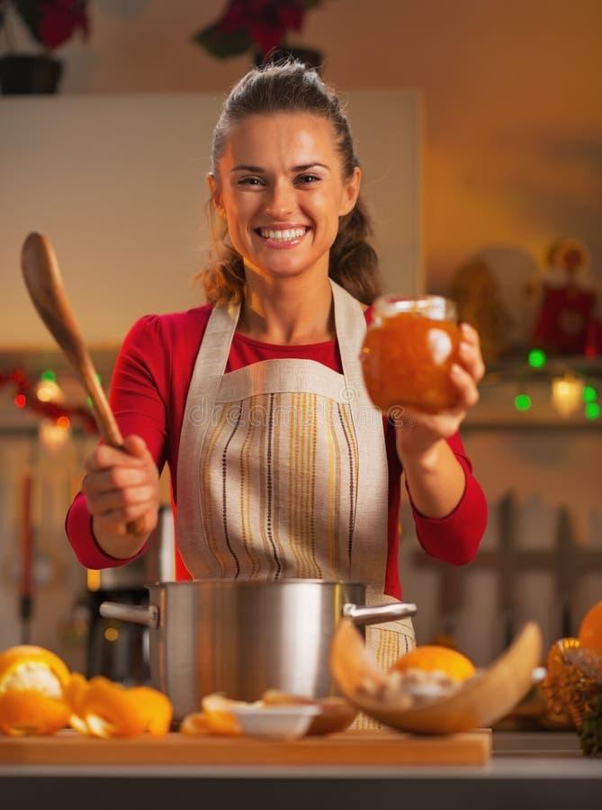 Gelukkige jonge huisvrouw die oranje jam in keuken tonen royalty-vrije stock foto's