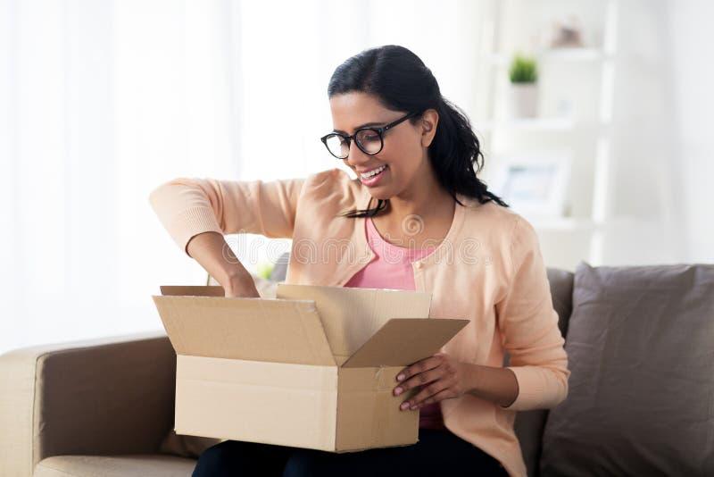 Gelukkige jonge Indische vrouw met pakketdoos thuis stock fotografie