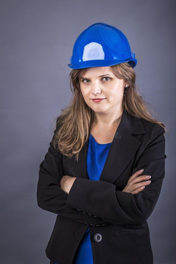 Gelukkige jonge ingenieursvrouw met bouwvakker en gevouwen wapens royalty-vrije stock afbeeldingen