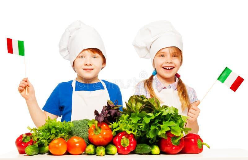 Gelukkige jonge Italiaanse koks met groene groenten royalty-vrije stock fotografie