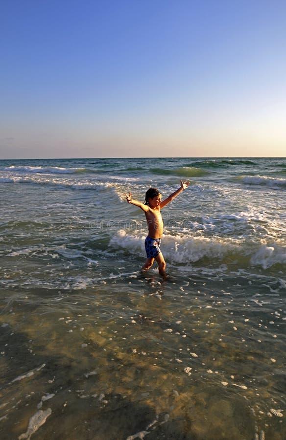 Gelukkige Jonge jongen bij het strand stock foto's