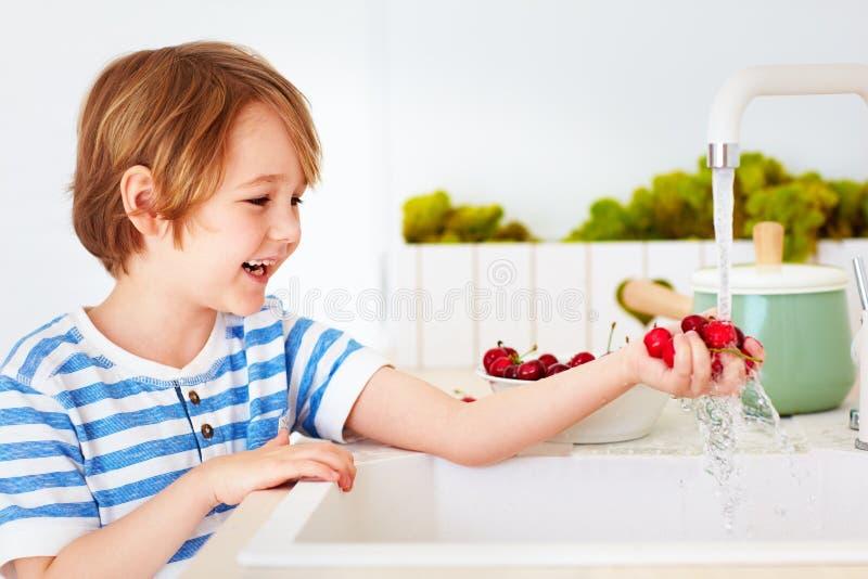 Gelukkige jonge jongen die het armvol zoete kersen wassen onder leidingwater in de keuken stock fotografie