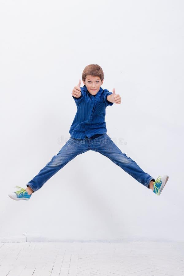 Gelukkige jonge jongen die op witte achtergrond springen stock afbeelding