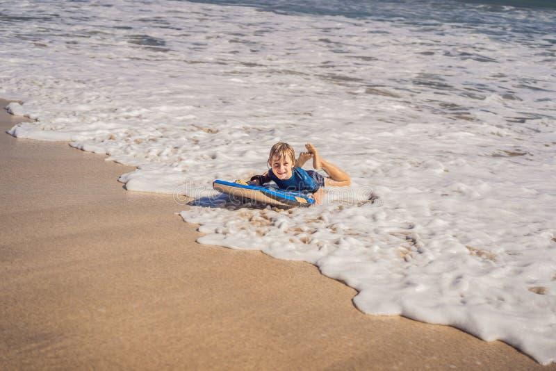 Gelukkige Jonge jongen die pret hebben bij het strand op vakantie, met Boogie-raad stock foto