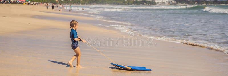 Gelukkige Jonge jongen die pret hebben bij het strand op vakantie, met Boogie-raadsbanner, LANG FORMAAT royalty-vrije stock afbeelding
