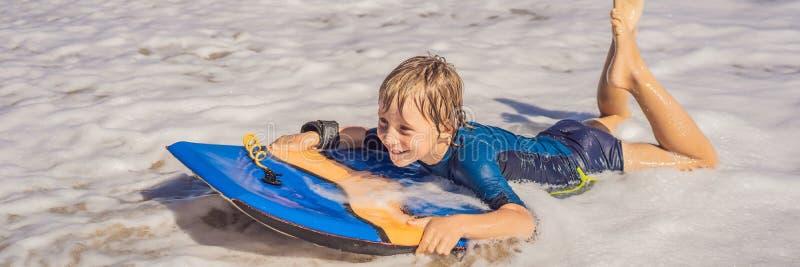 Gelukkige Jonge jongen die pret hebben bij het strand op vakantie, met Boogie-raadsbanner, LANG FORMAAT stock foto's