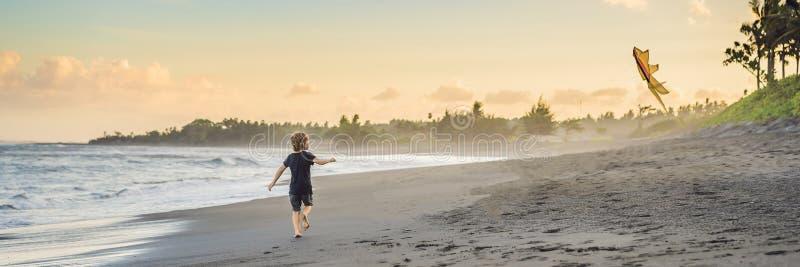 Gelukkige jonge jongens vliegende vlieger op het strand bij zonsondergangbanner, LANG FORMAAT royalty-vrije stock afbeeldingen