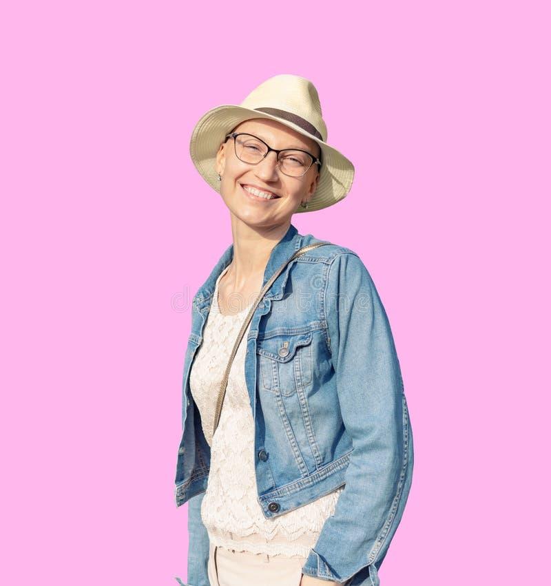 Gelukkige jonge Kaukasische kale vrouw die in hoed en vrijetijdskleding van het leven na overlevende borstkanker genieten Portret royalty-vrije stock foto's
