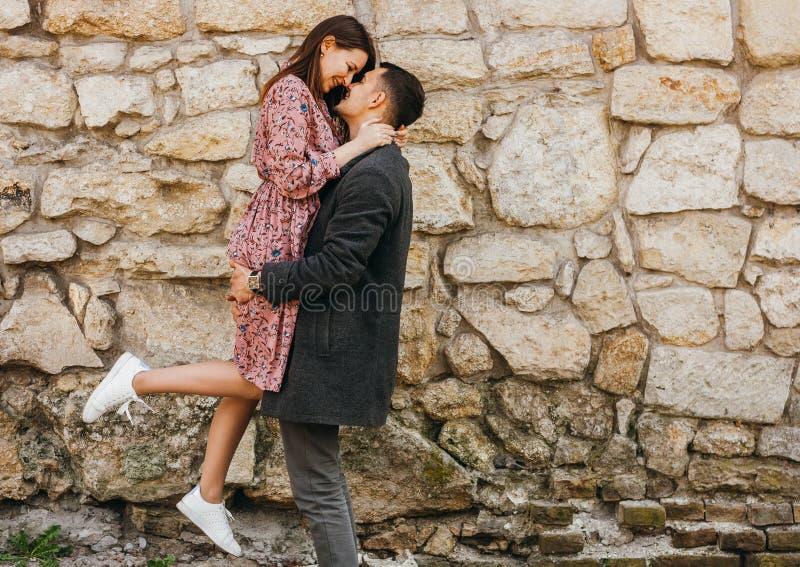 Gelukkige jonge man die zijn vrouw in zijn wapens houden tegen steenachtergrond stock fotografie
