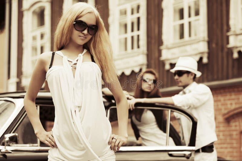 Gelukkige jonge manier blonde vrouw in witte kleding naast uitstekende auto royalty-vrije stock fotografie