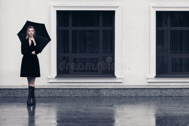 Gelukkige jonge maniervrouw die met paraplu in stadsstraat lopen royalty-vrije stock foto's