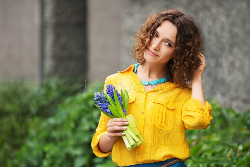 Gelukkige jonge maniervrouw in geel overhemd met boeket van bloemen royalty-vrije stock afbeeldingen