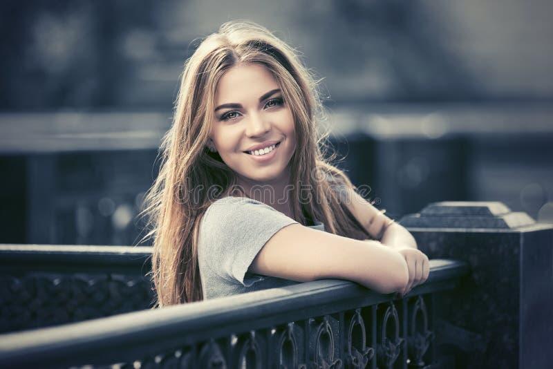 Gelukkige jonge maniervrouw in grijze t-shirt die op traliewerk leunen stock afbeelding