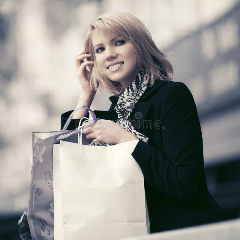 Gelukkige jonge maniervrouw met het winkelen zakken bij de wandelgalerij stock foto's