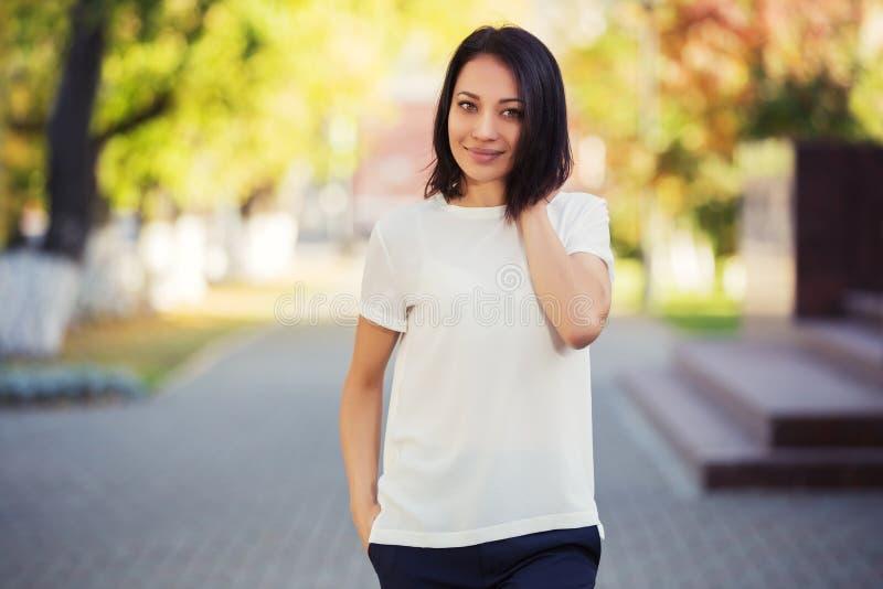 Gelukkige jonge maniervrouw in witte t-shirt op stadsstraat stock foto