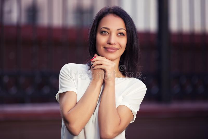 Gelukkige jonge maniervrouw in witte t-shirt op stadsstraat royalty-vrije stock afbeeldingen