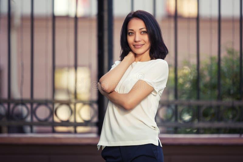 Gelukkige jonge maniervrouw in witte t-shirt op stadsstraat stock afbeeldingen