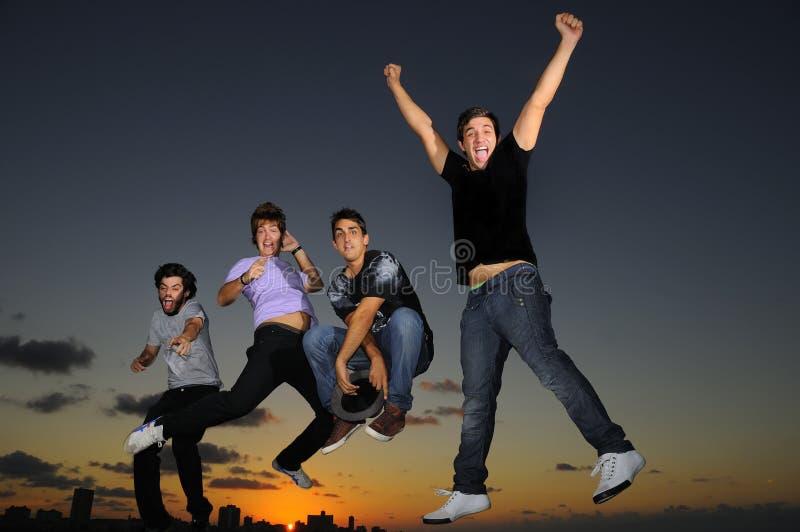 Gelukkige jonge mannelijke groep die in openlucht springt stock afbeeldingen
