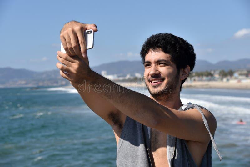Gelukkige jonge mannelijke toerist die een selfie neemt bij het strand stock foto's