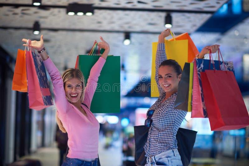Gelukkige jonge meisjes in winkelcomplex royalty-vrije stock afbeelding