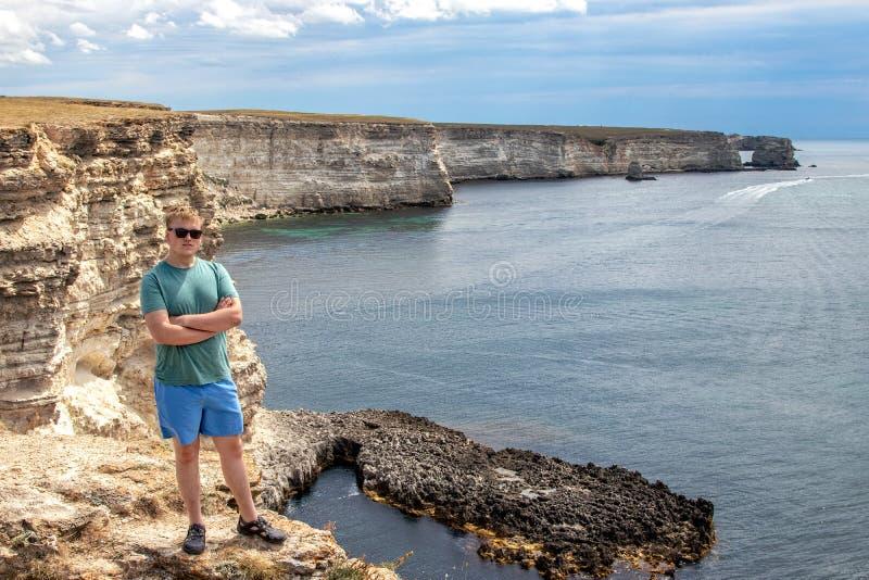 Gelukkige jonge mens die bovenop klip van mening van overzees genieten Bergen en Overzees stock afbeelding