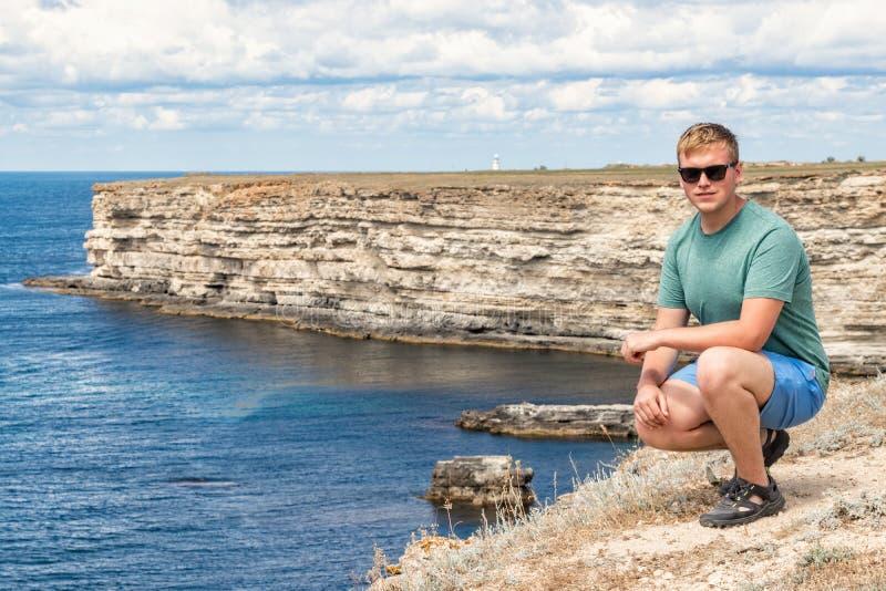 Gelukkige jonge mens die bovenop klip van mening van overzees genieten Bergen en Overzees stock foto's