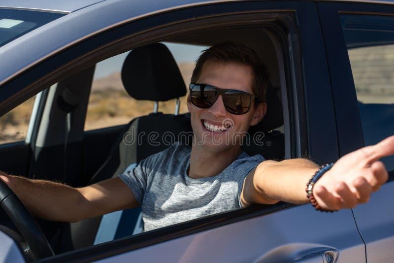 Gelukkige jonge mens die een gehuurde auto in de woestijn van Isra?l drijven royalty-vrije stock foto