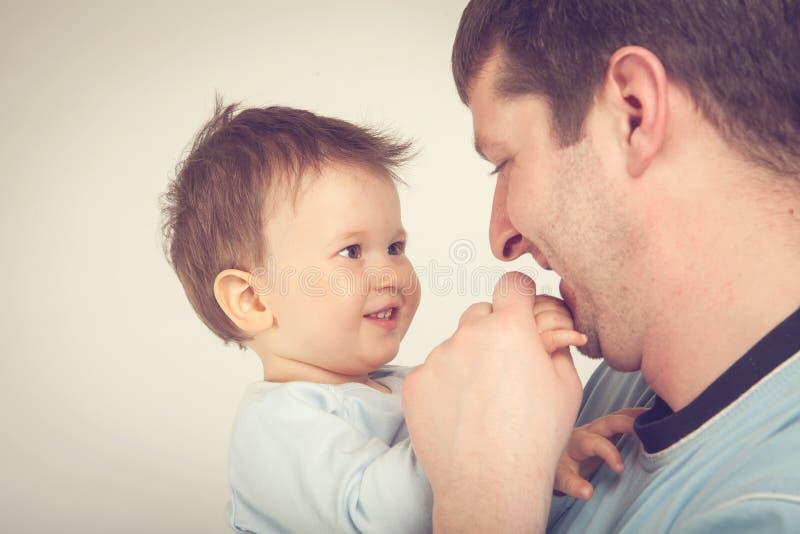 Gelukkige jonge mens die een glimlachende baby houden Vader en zoon royalty-vrije stock foto