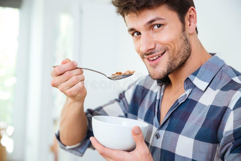 Gelukkige jonge mens die graangewassen met melk thuis eten royalty-vrije stock foto