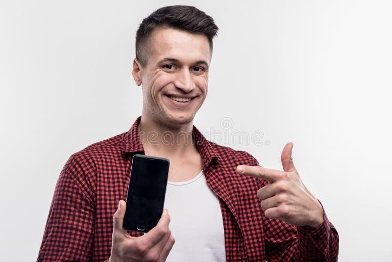 Gelukkige jonge mens die gelukkige holding voelen zijn nieuwe zwarte slimme telefoon stock afbeelding
