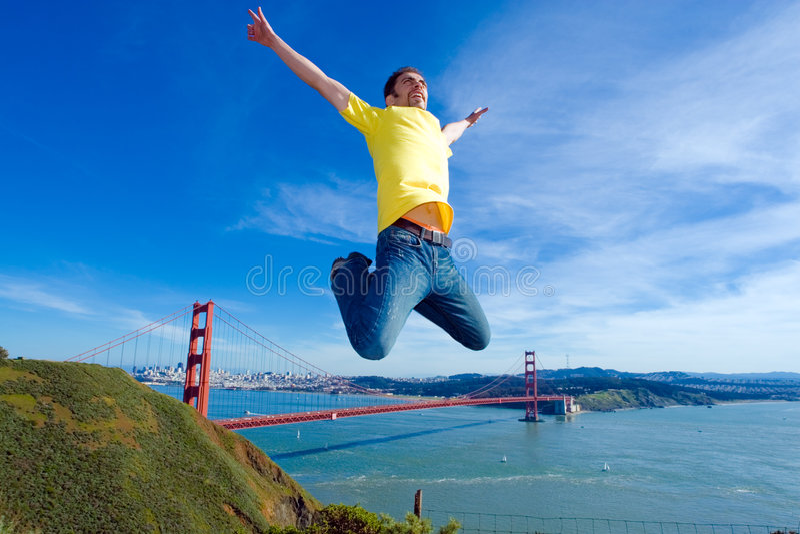 Gelukkige jonge mens die hoog in de lucht naast de Gouden brug van de Poort springt stock fotografie