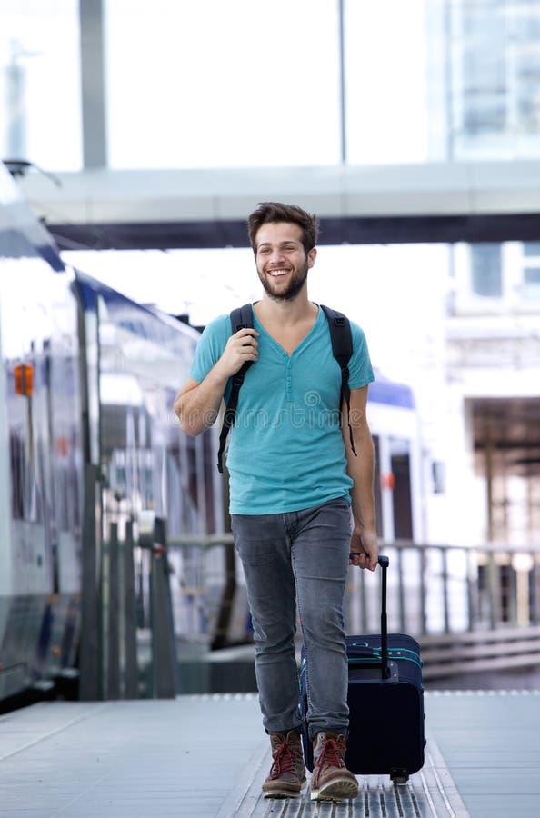 Gelukkige jonge mens die met koffer bij station lopen stock fotografie