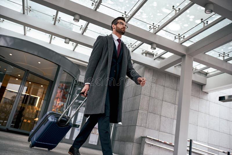 Gelukkige jonge mens die met reiszak van hotel aan luchthaven lopen royalty-vrije stock foto
