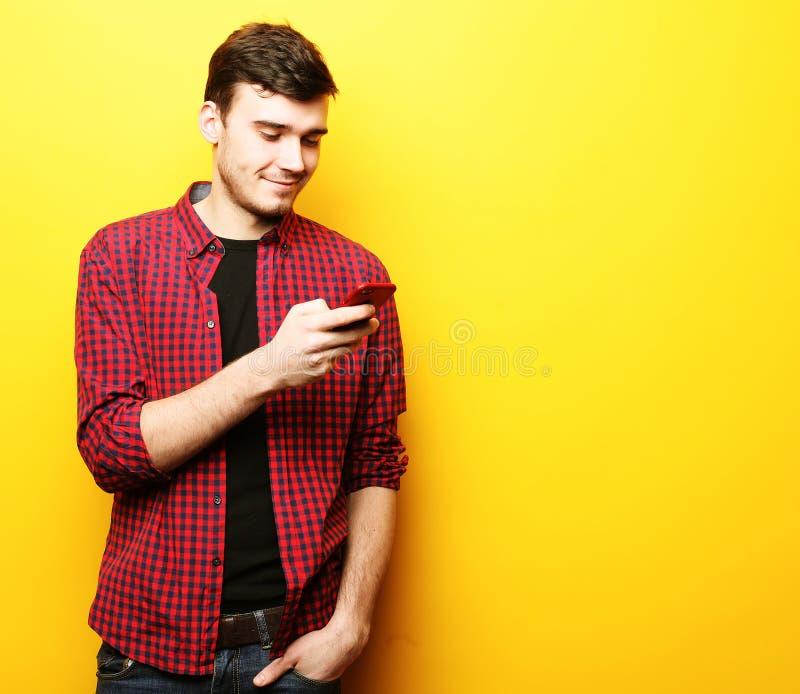 Gelukkige jonge mens die op celtelefoon spreken over gele achtergrond stock afbeelding