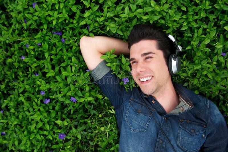 Gelukkige jonge mens die op gras liggen, die aan muziek luisteren stock fotografie