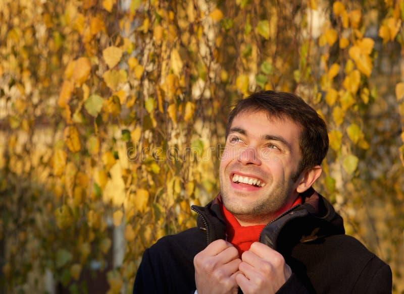 Gelukkige jonge mens die in openlucht met de winterjasje glimlachen stock foto