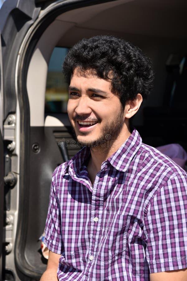 Gelukkige jonge mens die in openlucht op de rug van zijn auto zitten stock afbeelding