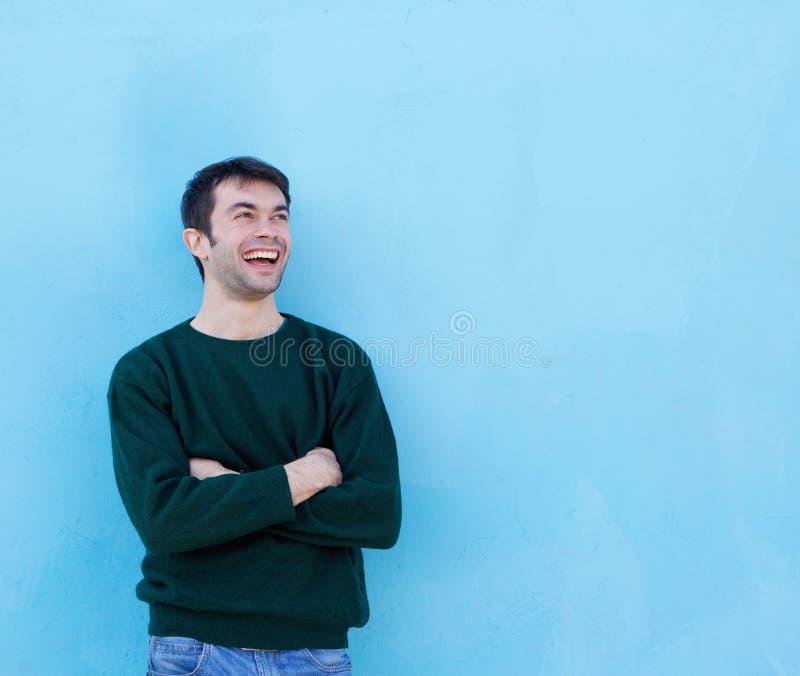 Gelukkige jonge mens die tegen blauwe achtergrond lachen stock fotografie