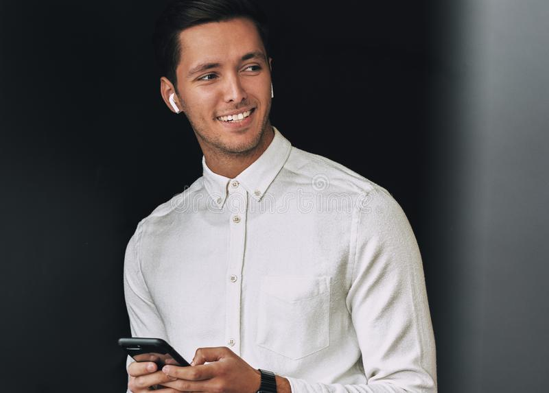 Gelukkige jonge mens die, texting berichten van zijn cellphone over studio zwarte achtergrond, met draadloze oortelefoons glimlac stock afbeelding