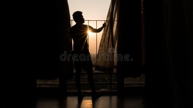 Gelukkige jonge mens die van een mooie zonsondergang van zijn flatbalkon genieten met zonstralen die door zijn schouders overgaan royalty-vrije stock foto's
