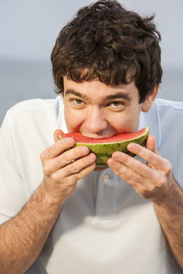 Gelukkige, jonge mens die watermeloen eten stock foto