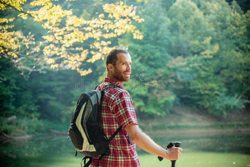 Gelukkige jonge mens die zich door het bergmeer dat door weelderig groen bos wordt omringd bevinden die over zijn schouder kijken royalty-vrije stock fotografie