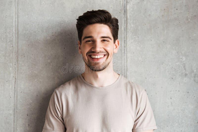 Gelukkige jonge mens die zich over grijze muur bevinden royalty-vrije stock afbeelding