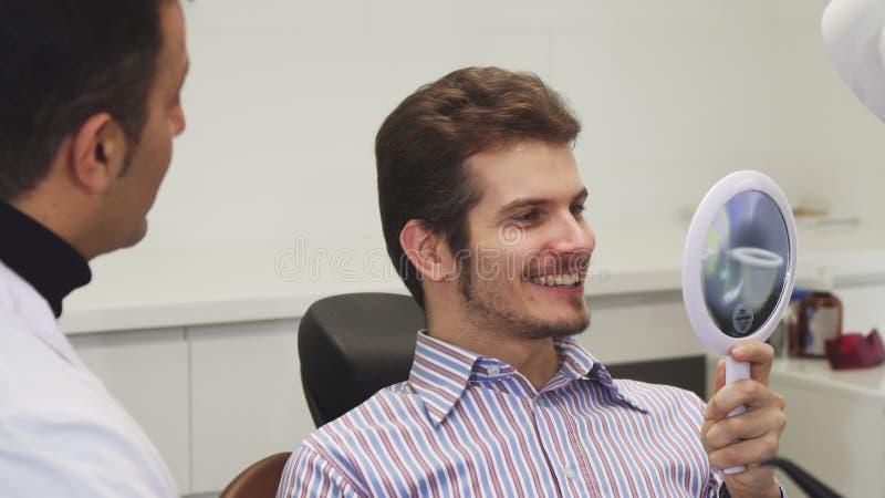 Gelukkige jonge mens die zijn gezonde glimlach controleren op het tandkantoor royalty-vrije stock foto's