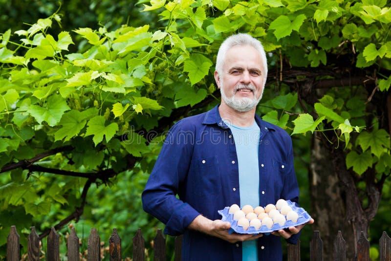 Gelukkige jonge mens die zijn kip en mand van eieren in zijn GA houden royalty-vrije stock foto