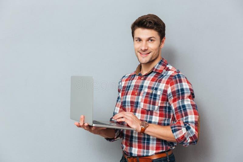 Gelukkige jonge mens in geruit overhemd die en laptop bevinden zich houden royalty-vrije stock afbeelding