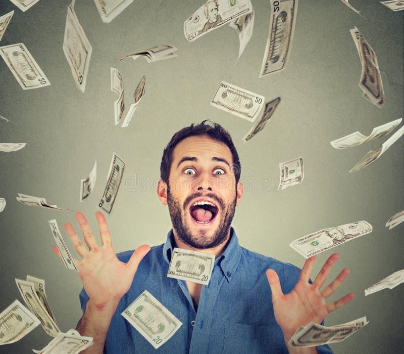 Gelukkige jonge mens het gaan gekke het gillen super opgewekt onder geldregen royalty-vrije stock afbeelding